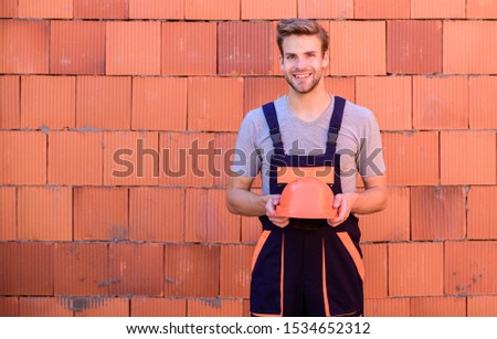 carry out repairs. worker brick wall background. building and construction. professional repairman hard hat. man builder in work clothes. man build house. skilled architect repair and fix.