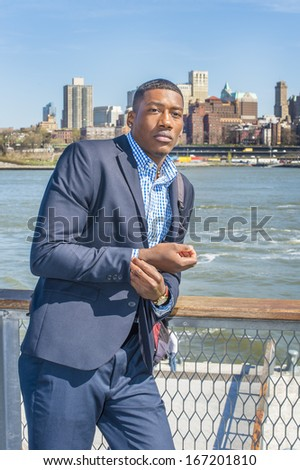 stock-photo-carrying-a-bag-a-young-black-businessman-is-standing-by-the-river-looking-forward-traveling-167201810.jpg