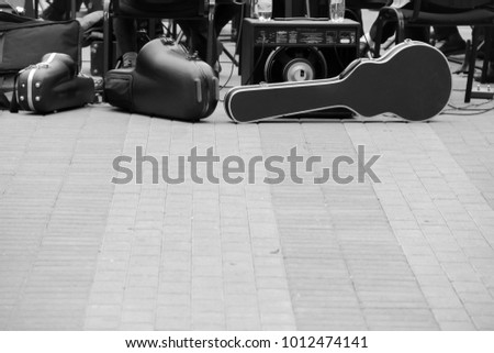 carrying case for cello, music speakers, other musical equipment. A band preparing to play on the street,shoot in black and white