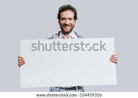 Carrying copy space. Young confident man in smart casual clothes holding blank flipchart and smiling while standing against grey background