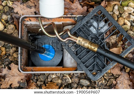 Carrying out emergency cleaning of a blocked drainage gulley outlet with a Drain rod with  plunger attachment  Stockfoto ©