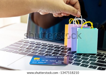 Carrying paper shopping bag with finger and mock up of credit card on laptop keyboard. Consumer can buy products anywhere anytime from seller using web browser. Online shopping and e-commerce concept.
