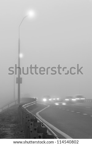 Cars are moving along the foggy road - stock photo