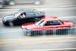 Cars at speed. Street racing. Blurred cars at speed.