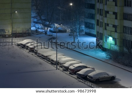 cars covered with snow in the courtyard under the lantern, winter night