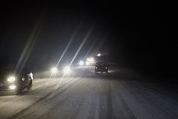 Cars drive on the highway in heavy snowfall at black night. Shining headlights in the dark. Driving in the dangerous conditions of the north