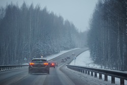 Cars drive on the road in snow storm in the evening. Snow is flying, driving in the dangerous conditions of the north