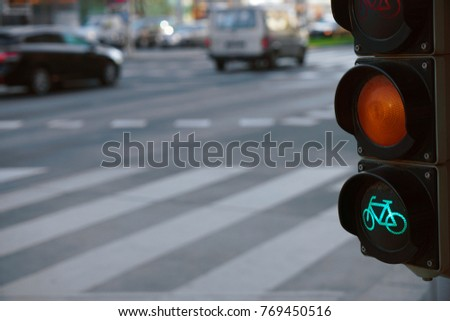 cars drive on the street in the city center in a beautiful light by a traffic light for cyclist with red green and orange light #769450516