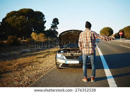 Cars - driver trying stop car in travel because his car broken. Young man stand on freeway and shows thumbs up. Young interracial man in their twenties, Caucasian man.