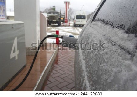 cars in the snow at a gas station in the winter, a gun in the gas tank, the background image of a small depth of field