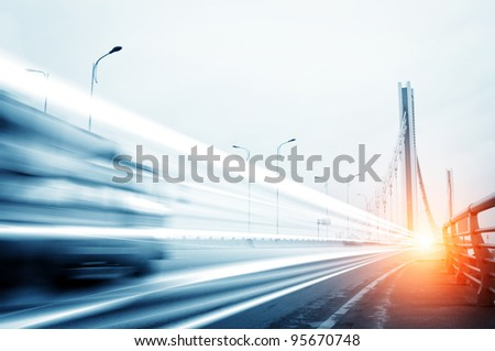 cars light trails on the modern bridge at dusk - stock photo
