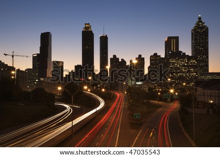 Cars on a freeway traveling through downtown at night. Horizontal shot. - stock photo