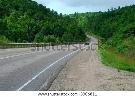 Cars On A Highway Running Downhill Through Wooded Hill Country
