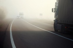 Cars on the highway in the fog. Dangerous overtaking. Scene with traffic offense