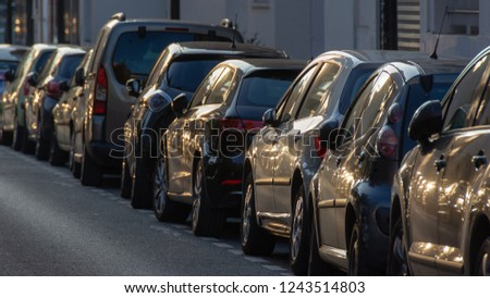 Cars parked along a street at sunset #1243514803