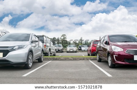 Cars parked in asphalt parking lot. Trees, white cloud blue sky background, empty space for car parking. Outdoor parking lot with green environment. nature travel transportation technology concept Stockfoto ©