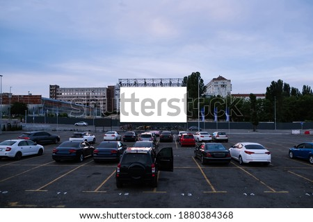 Cars parked in front of drive-in cinema screen, top view. Free time, leisure and entertainment concept