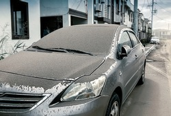 cars parked on the side of the dormitory affected from Volcanic dust fall, dirty surface car in the morning, ashes falling , concept dirty car, Blur background