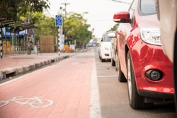 Cars parked on the urban street side and there Bike lane in city street