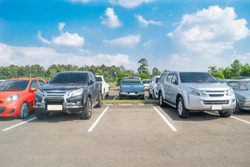 Cars parking in asphalt parking lot. Trees, white cloud blue sky background, empty space for car parking. Outdoor parking lot with green environment. nature travel transportation technology concept