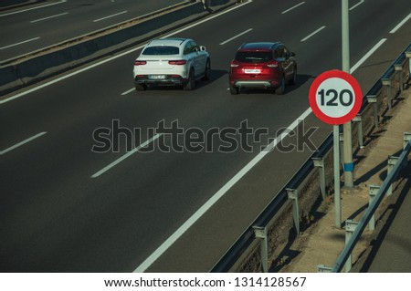 Cars passing through multi lane highway and SPEED LIMIT signpost, on sunset in Madrid. Capital of Spain this charming metropolis has vibrant and intense cultural life. #1314128567