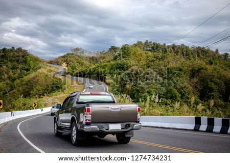 Cars running on the beautiful road along the mountain, Rear view of pickup truck on wavy road