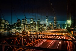 Cars speeding at sunset on Brooklyn Bridge, Manhattan. One of the most iconic bridges in the world, a must see attraction when visiting New York.