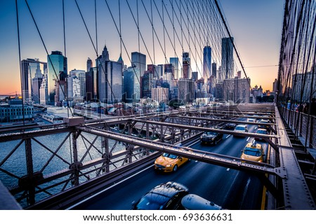 Cars speeding at sunset on Brooklyn Bridge, Manhattan. One of the most iconic bridges in the world, a must see attraction when visiting New York. - Shutterstock ID 693636631