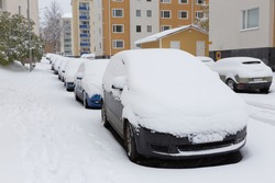 Cars stands on a snow-covered road in a wintertime cloudy day. Snowfall in the city, cars under the snow.