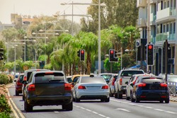 cars stopped at a red traffic light signal in the summer hot midday with a shallow depth of field