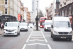 Cars, white vans driving on a road, London, street, blurred background, city, busy.