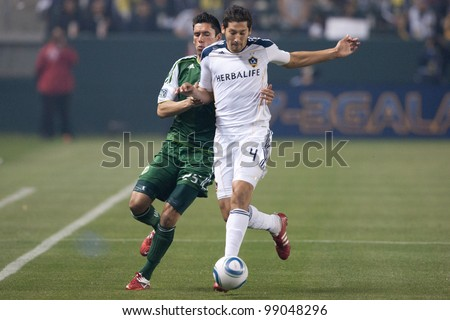 CARSON, CA. - April 23: Los Angeles Galaxy D Omar Gonzalez #4 & Portland Timbers D Steve Purdy #25 during the MLS game on April 23 2011 at the Home Depot Center. - stock photo