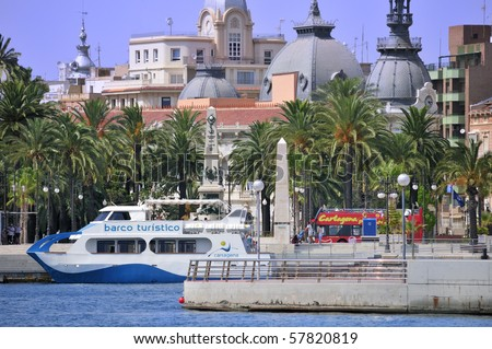 Cartagena, Spain. View from the port showing historic buildings official sightseeing bus and tourist boat.