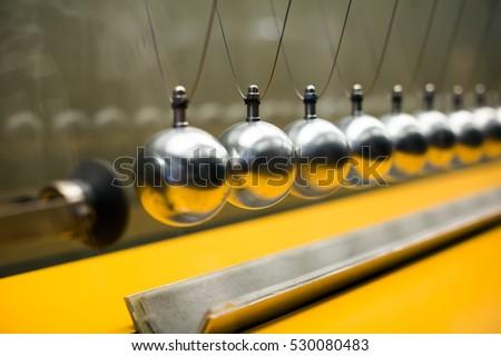 Cartesian impulse conservation law experiment metallic balls #530080483