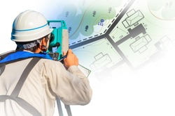 Cartography. Engineer-surveyor with equipment. A man makes maps. The cartographer works with a theodolite or total positioning station. A man in a white helmet on the background of the map.