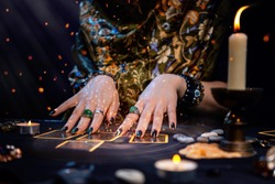 Cartomancy. A fortune teller reads Tarot cards. On the table are candles and fortune-telling objects and sparks. Hands close up. The concept of divination, astrology and esotericism