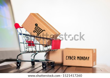 Carton box and and trolley on laptop computer. Online shopping and Cyber Monday shopping concept