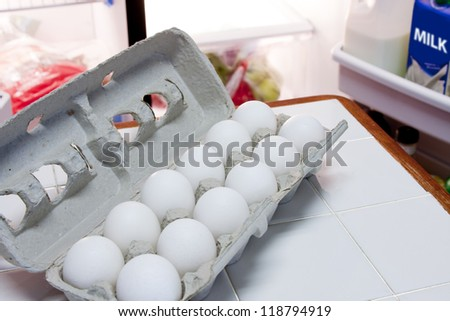 Carton of eggs and half gallon of milk in refrigerator