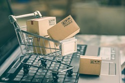 Cartons in a shopping cart on a laptop keyboard. Ideas about online shopping, online shopping is a form of electronic commerce that allows consumers to directly buy goods from a seller over internet.