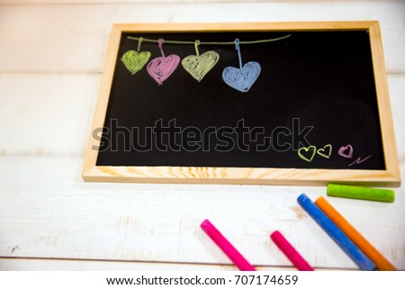 Cartoon heart draw by colorful chalk on wooden blackboard. blackboard and colorful chalk put on white table,  #707174659