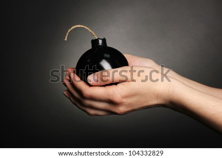 Cartoon style bomb in hands on black background
