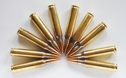 Cartridges with armor piercing bullets in a semi circle on a white background