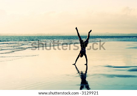 Cartwheel on a deserted beach - stock photo