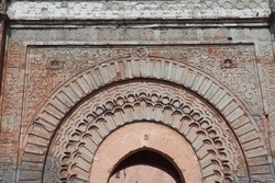 Carved ancient stone wall ornament, oriental structure details and moroccan art design at historic old archway gate entrance Bab Agnaou monument landmark in arabian city medina of Marrakech, Morocco.