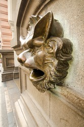Carved bronze head on the side of a building depicting the head of a man like face of a wolf