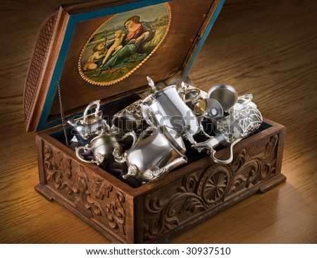 Carved chest with silver tableware - stock photo
