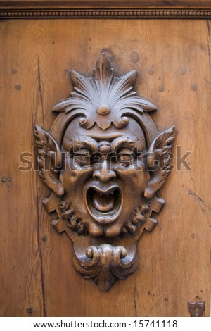 Carved gargoyle adorning a wooden door in Siena, Italy