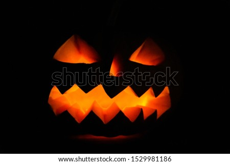 Carved halloween pumpkin jack-o-lantern glows in darkness