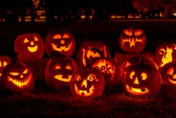 Carved Halloween pumpkins lit with candles sitting on fallen leaves and hay bales