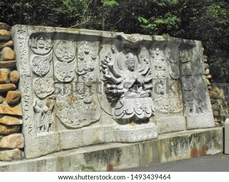 Carved in stone image of Goddess Guanyin with several pairs of hands in Nanshan Buddhism Center, Hainan island. Place of pilgrimage. Travel to China.